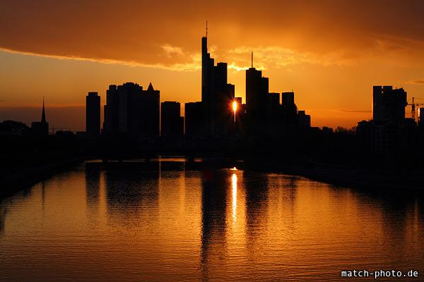 Skyline Frankfurt mit Reflektion der Hochhäuser und der Sonne im Main.
