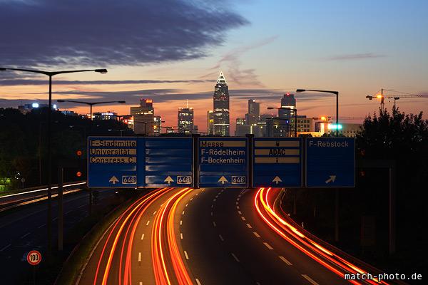 Frankfurt Hochhäuser während Morgendämmerung mit Berufsverkehr.