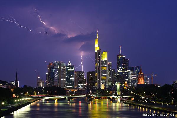 Gewitter mit Blitz und Wetterleuchten vor Skyline Frankfurt. Messeturm, Commerzbank-Tower und Frankfurter Büro Center.