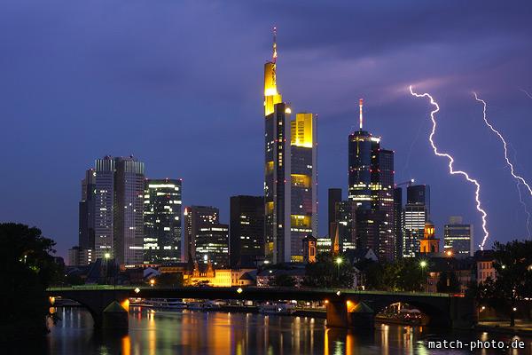 Frankfurter Hochhäuser im Nachthimmel. Blitzeinschlag neben den Deutsche Bank Türmen. Blick über den Main.
