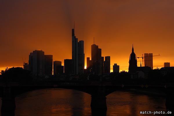 Frankfurter Hochhäuser vor orange leuchtendem Himmel mit Sonnenstrahlen.