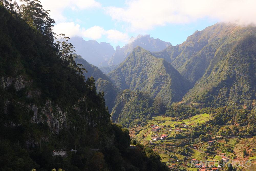 Wolken über den Bergen. Kleines Dorf am Hang im Vordergrund