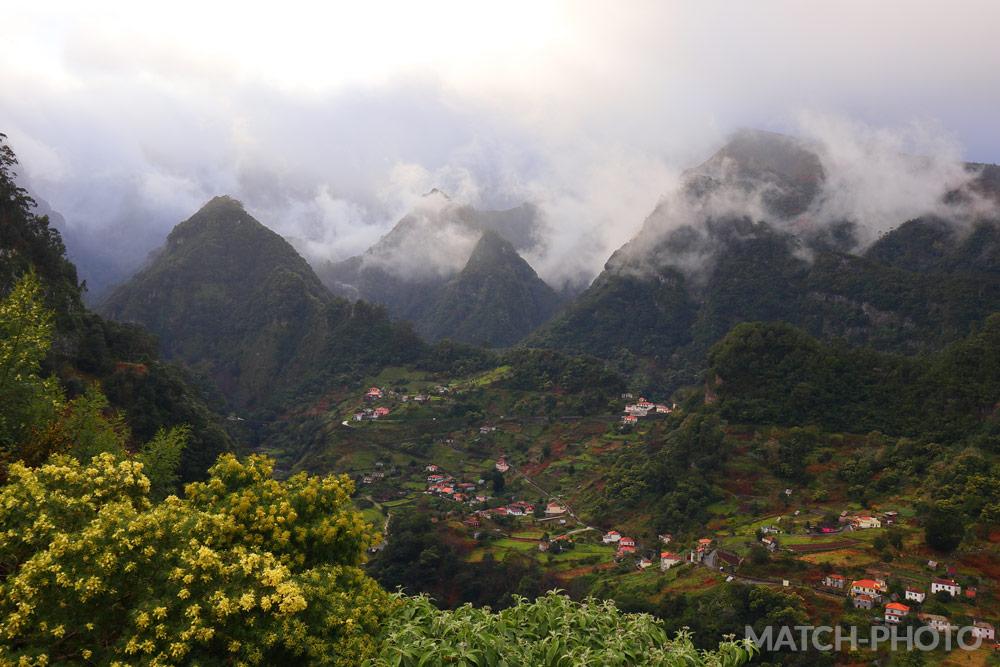 Wolkenverhangene Bergspitzen in der Abenddämmerung.