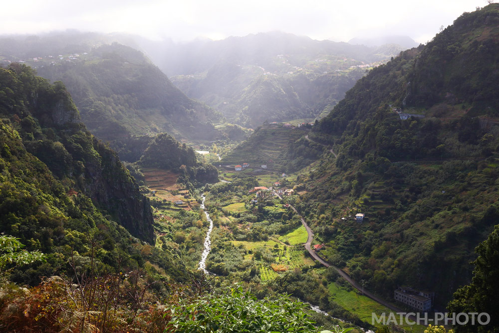 Blick hinab auf ein Dorf im Tal.