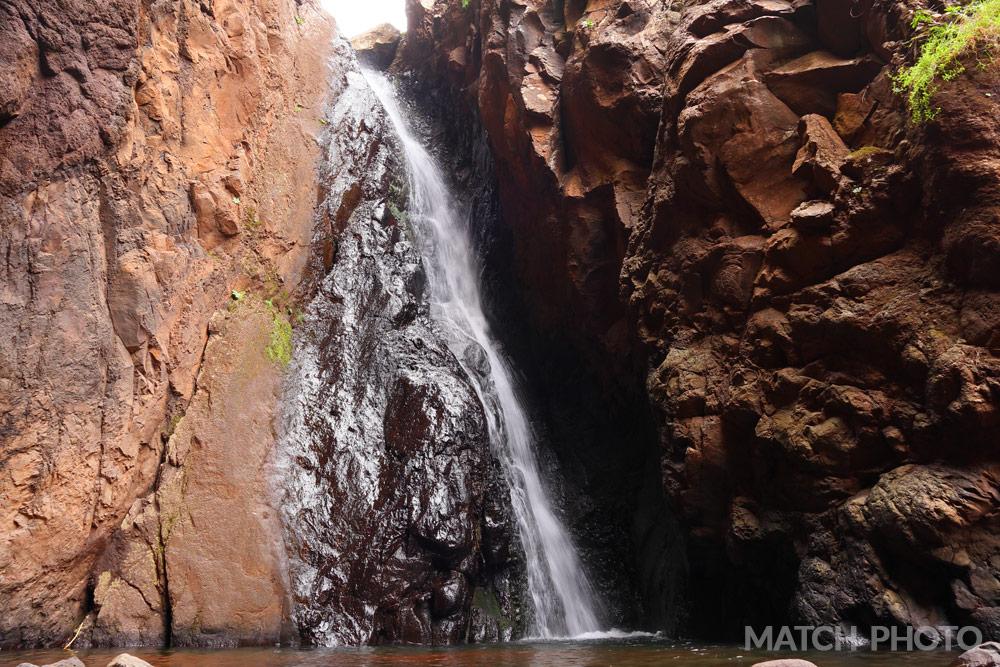 Wasserfall an einer Felswand. Nasser Stein glänzt und schimmert.